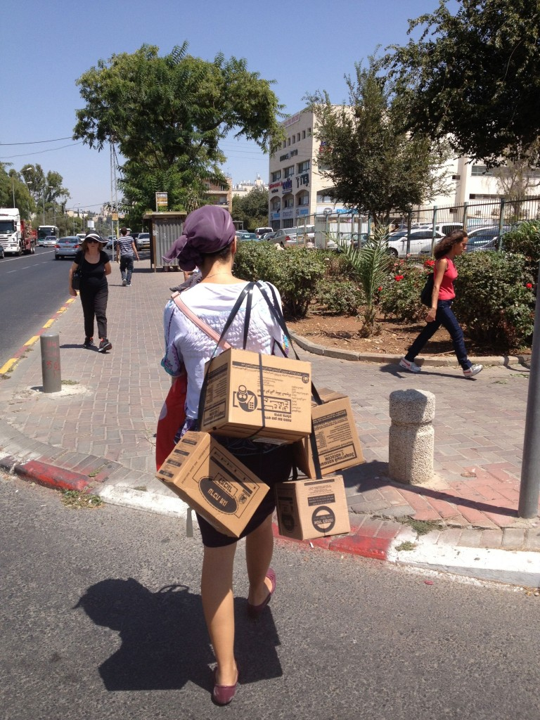 A mother returning home from the gas mask distribution center in Jerusalem with gas masks for her family